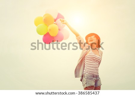 Young hipster woman holding balloons she smiley with it below the sky - stock photo
