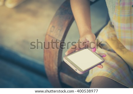 Young hipster woman holding smartphone on her right hand while sitting on wood bench in morning time with vintage filter effect - stock photo