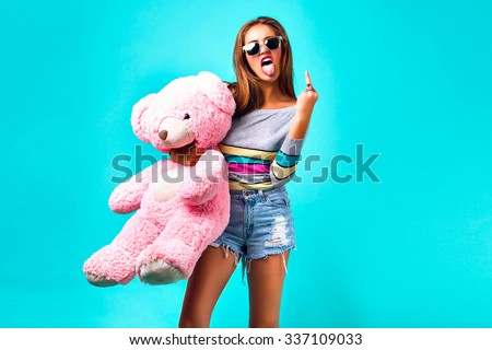Young hipster woman playing with big fluffy pink toy bear, showing tongue and middle finger, wearing sexy mini shorts and sunglasses, cheeky emotions, yo, cool, crazy. - stock photo