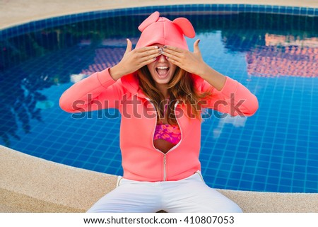 young hipster woman sport style sitting at pool, pink neoprene hoodie, stylish apparel, sunglasses, fun, summer, funny face, close up, expression, laugh, smiling, closing eyes, going crazy - stock photo