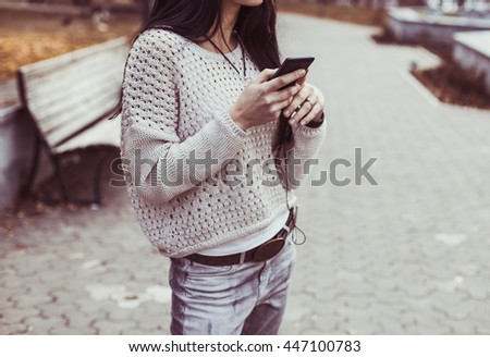 Young Hipster woman using her phone in the city at autumn time - stock photo