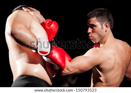 Young Hispanic boxer throwing an uppercut and hitting his opponent during a box fight - stock photo