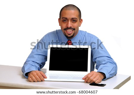 Young Hispanic business man seated at his desk holding his laptop facing forward, showing product message. - stock photo