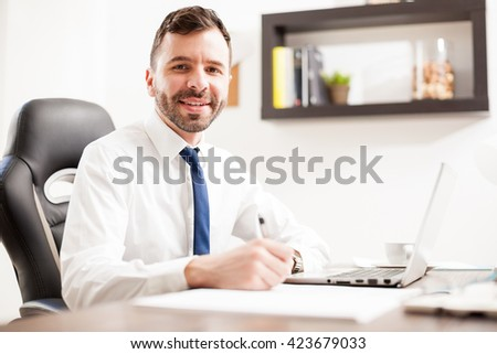 Young Hispanic businessman signing a few documents and taking some notes in his office and smiling - stock photo
