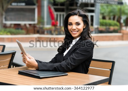 Young Hispanic businesswoman in her twenties outdoors working - stock photo