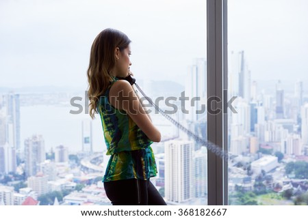 Young hispanic businesswoman in modern office building, with a beautiful sight of the city. She holds a wired telephone with long wire and looks outside window - stock photo