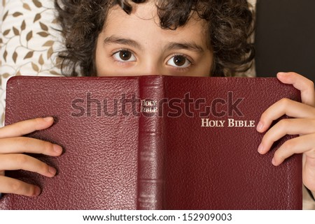 Young Hispanic child reading and studing the Holy Bible at home. Daily devotional and reverence of a boy. Taking a break and meditating on the word of God. Love of a child for his Creator in Heaven - stock photo