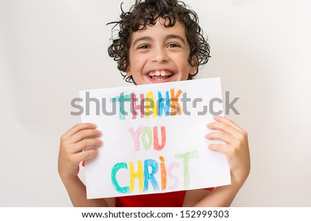 Young Hispanic child smiling and expressing positivity. He is thanking God and Jesus for the joy he experiments in his life. Solid relationship with the Savior since childhood - stock photo