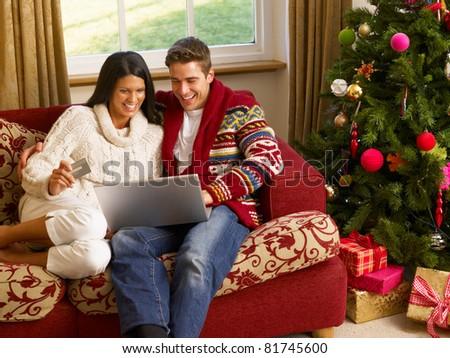 Young Hispanic couple Christmas shopping online - stock photo