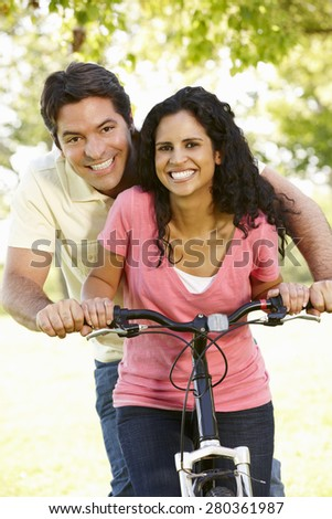 Young Hispanic Couple Cycling In Park - stock photo