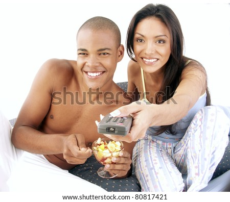 Young hispanic couple enjoying and eating fruit salad on bed. Young hispanic woman holding a remote control. Young couple sharing and watching television. - stock photo