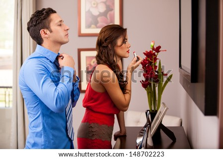 Young Hispanic couple getting ready to go out in front of the mirror - stock photo