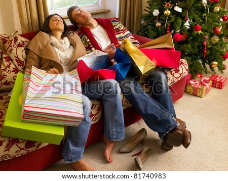 Young Hispanic couple resting after Christmas shopping - stock photo