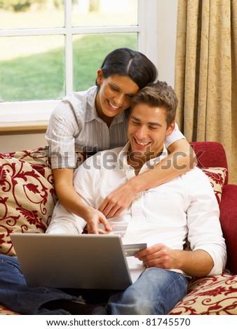 Young Hispanic couple shopping online - stock photo