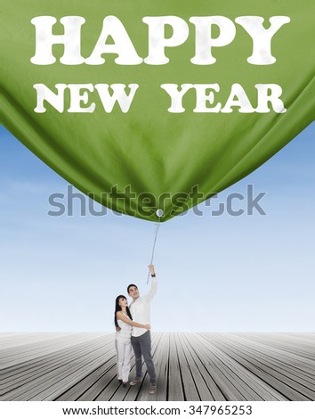 Young hispanic couple standing outdoors and pulling a banner new year - stock photo