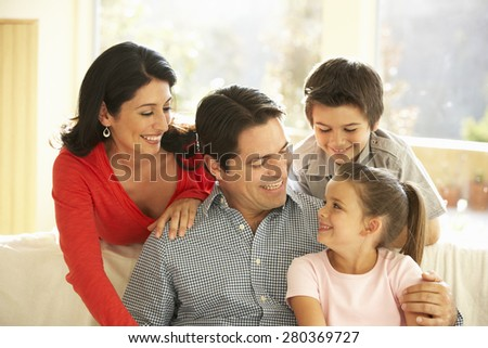 Young Hispanic Family Relaxing On Sofa At Home - stock photo