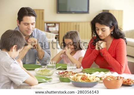 Young Hispanic Family Saying Prayers Before Meal At Home - stock photo