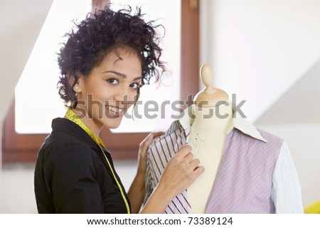 Young hispanic female dressmaker adjusting clothes on tailoring mannequin and smiling at camera. Horizontal shape, side view, waist up - stock photo