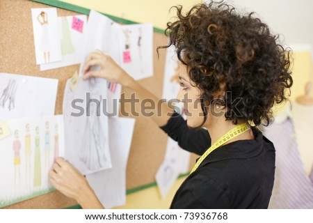 Young hispanic female dressmaker preparing show attaching drawings and sketches on board. Horizonta shape, side view, head and shoulders - stock photo