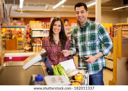 Young Hispanic man taking a credit card out of his wallet to pay for groceries at a supermarket - stock photo