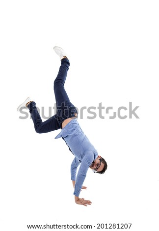 young hispanic man with blue shirt and glasses doing a cartwheel isolated over white - stock photo
