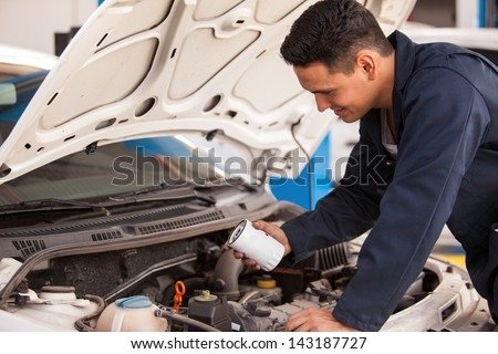 Young Hispanic mechanic changing the oil filter of a car at an auto shop - stock photo