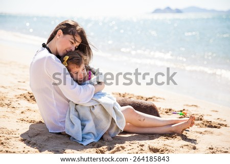Young Hispanic mother relaxing at the beach and embracing her little daughter on a sunny day - stock photo
