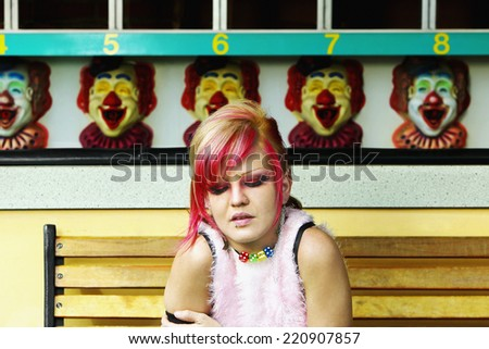 Young Hispanic punk female sitting in front of carnival booth - stock photo