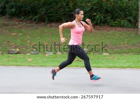 Young hispanic woman doing sprinting exercise in park - stock photo