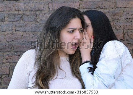 Young hispanic woman whispering a secret to her friend. Surprised expression. - stock photo