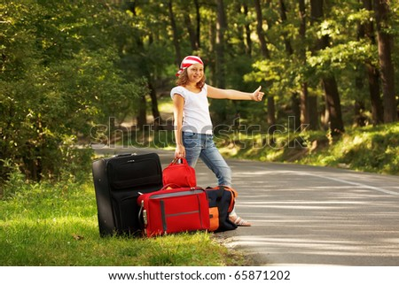 Young hitch-hiker girl standing on road side afternoon in forest with bags - stock photo