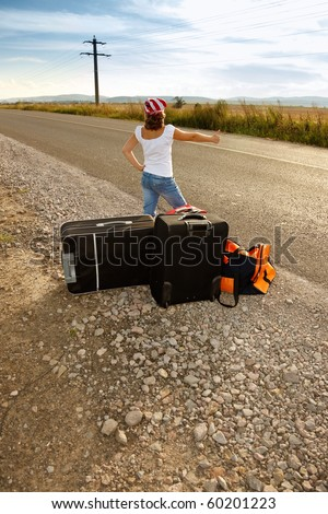 Young hitch-hiker girl standing on road side afternoon with suitcases - stock photo