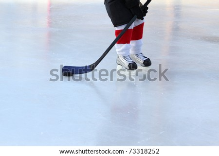Young hockey player practising on a frozen pond - stock photo