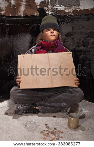 Young homeless boy on the street with a sign waiting for charity money - stock photo