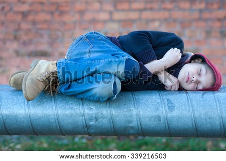 young homeless boy sleeping on a heating pipe, city, street - stock photo