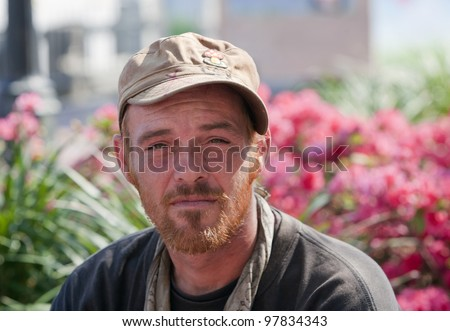 Young homeless man sitting outside during the daytime - stock photo