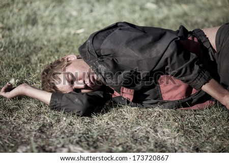 young homeless man sleeping - stock photo