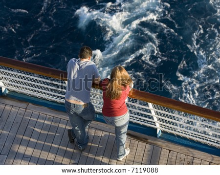Young honeymoon couple on the stern of a cruise ship. - stock photo