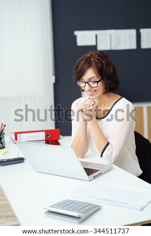 Young Hopeful Businesswoman Sitting at the Table with Laptop Computer, Showing Praying Hands Gesture with Happy Face. - stock photo