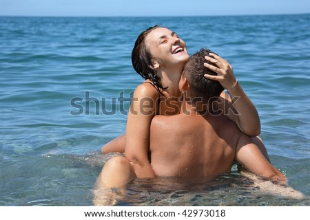 young hot woman sitting astride man in sea near coast, closed eyes - stock photo