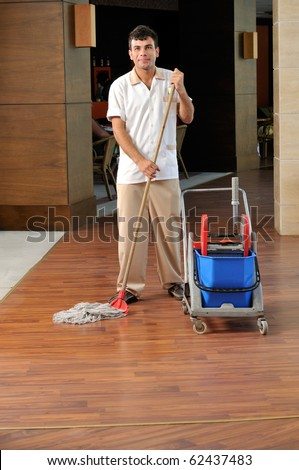 Young housekeeper mobbing the floor - a series of HOTEL images. - stock photo