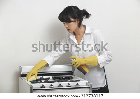 Young housemaid cleaning stove against gray background - stock photo