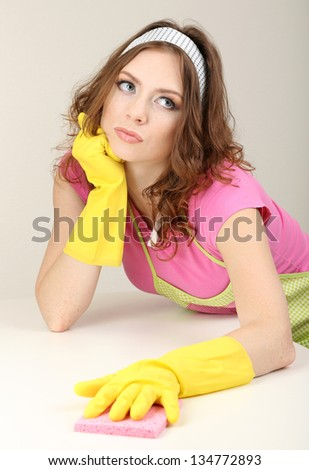 Young housewife cleaning up table at home on grey background - stock photo