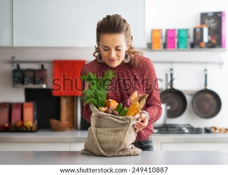Young housewife enjoying freshness of local market purchases - stock photo