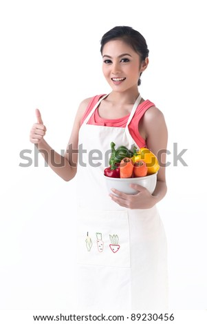 Young housewife holding a bowl of vegetable and thump up - stock photo