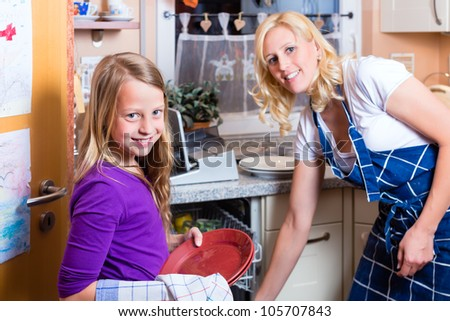 Young housewife is doing the dishes with dishwasher, her daughter is helping her - stock photo