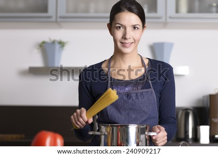 Young housewife preparing a healthy Italian pasta standing at the stove with a pot full of spaghetti with fresh vegetables in the foreground smiling happily at the camera - stock photo