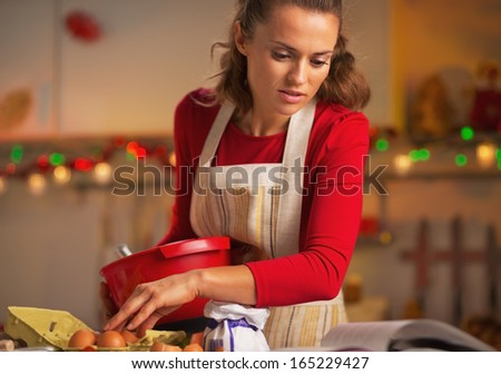 Young housewife preparing christmas dinner in kitchen - stock photo