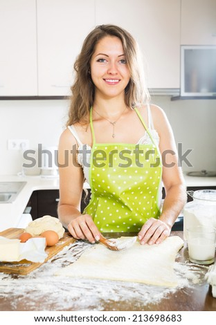 Young housewife preparing dough for baking - stock photo