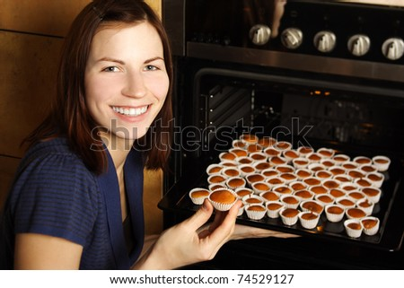young housewife taking cupcakes from oven and smiling - stock photo